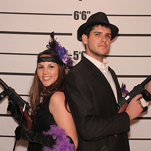 Miami Murder Mystery party guests pose for mugshots